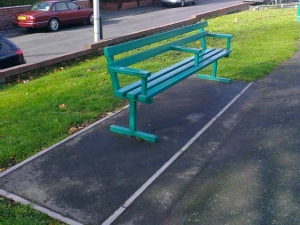 Metal bench with tarmaced area to accomodate wheelchairs